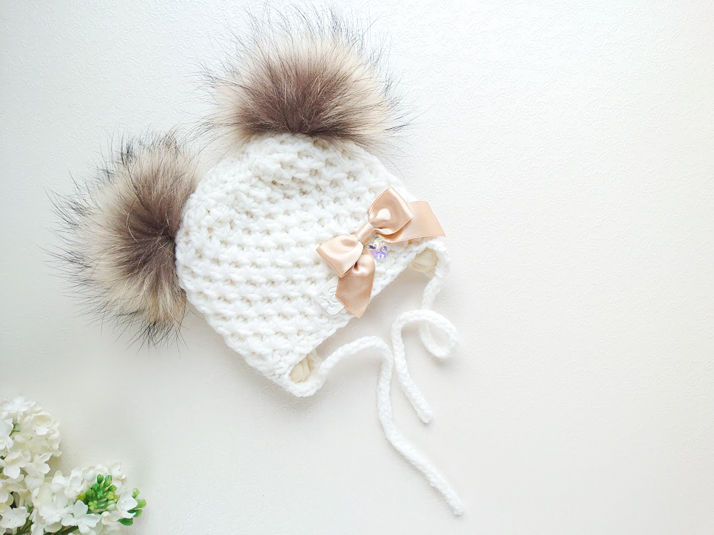 Türdukute valge kootud talvemüts beežide pruunide tuttidega ja lipsuga